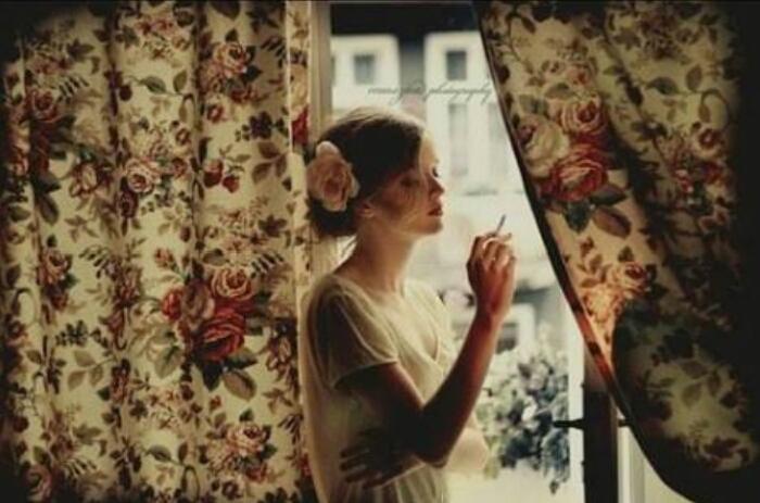 Фото девушка курит у окна.